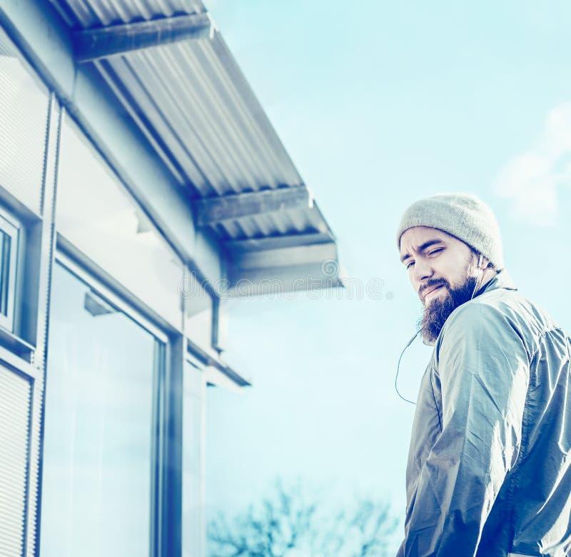 Junger Mann, der auf der Terrasse des Penthauses, auf Hintergrund des blauen Himmels steht lizenzfreie stockfotos