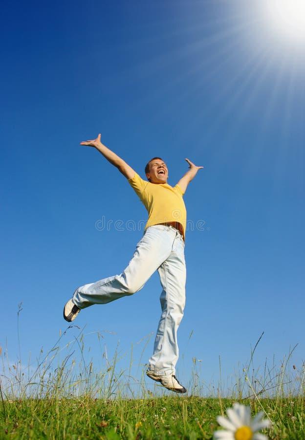 Junger Mann, der auf die Wiese springt lizenzfreies stockfoto