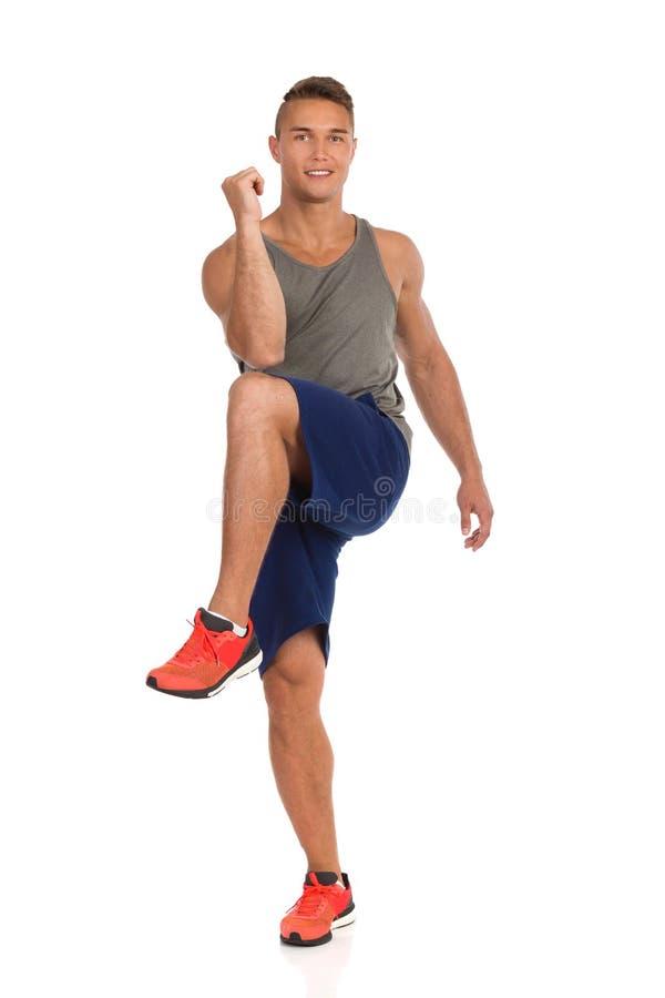 Junger Mann, der auf einem Bein steht und mit seinem Ellbogen zum Knie sich ber?hrt lizenzfreie stockbilder