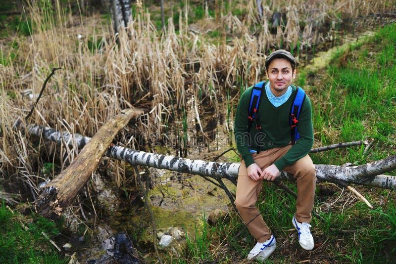 Junger Mann, der auf einem gefallenen Baumstamm unter den Bäumen genießen Natur sitzt lizenzfreies stockbild