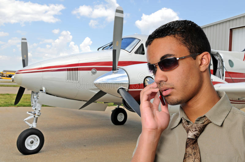 Junger Mann, der auf einem Handy am Flughafen spricht lizenzfreies stockfoto