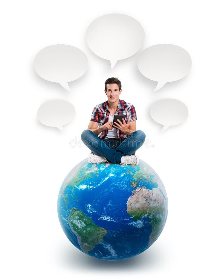 Junger Mann, der auf einem Planeten mit einer Tablette sitzt vektor abbildung