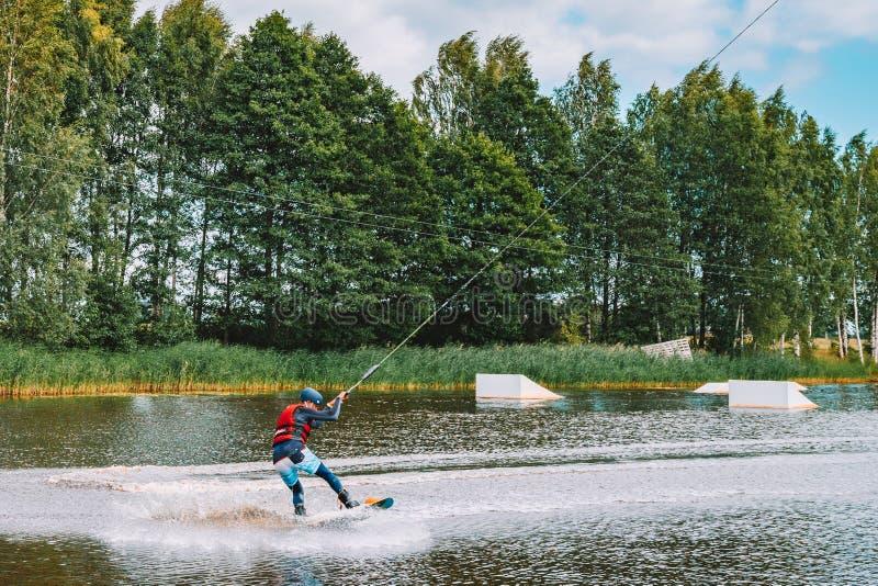 Junger Mann, der auf einem See wakeboarding ist stockfotos