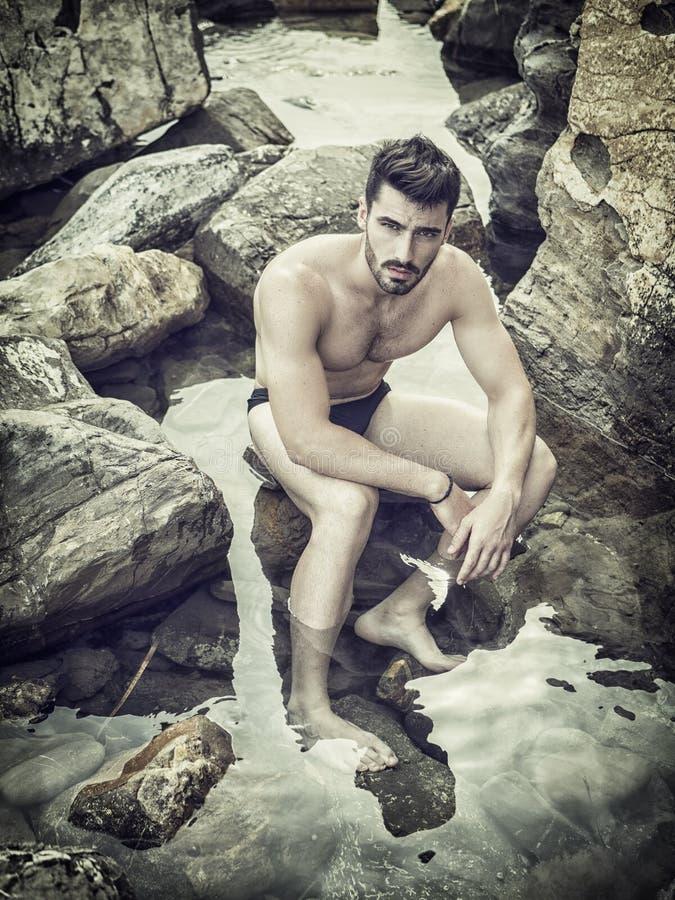 Junger Mann, der auf einem Strand allein sitzt lizenzfreies stockfoto