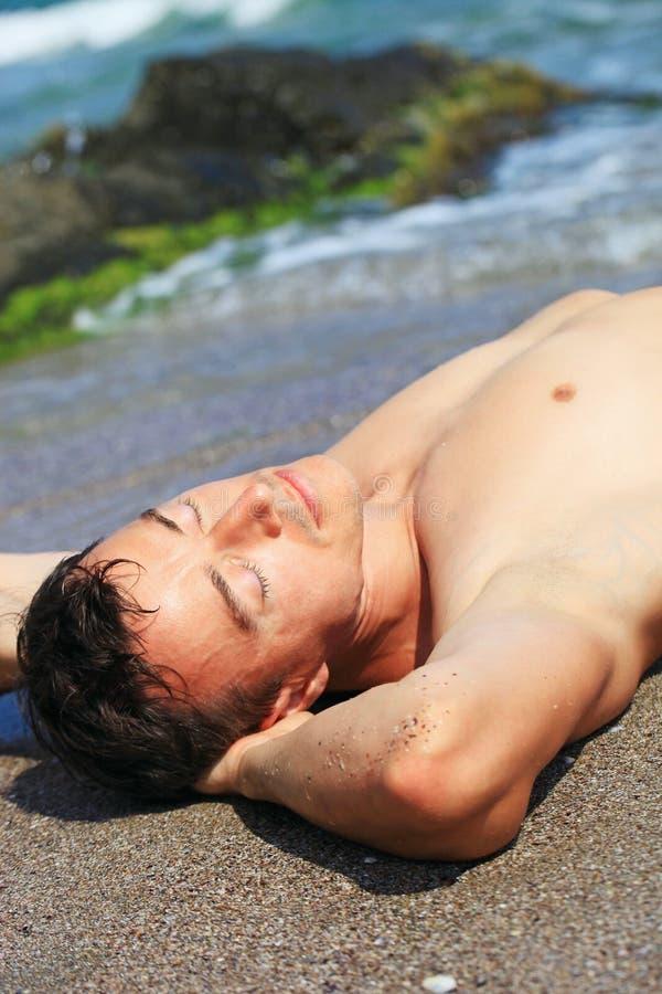 Junger Mann, der auf einem Strand ein Sonnenbad nimmt lizenzfreies stockbild