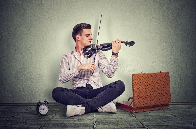 Junger Mann, der auf einer schwarzen elektronischen Violine spielt lizenzfreies stockfoto