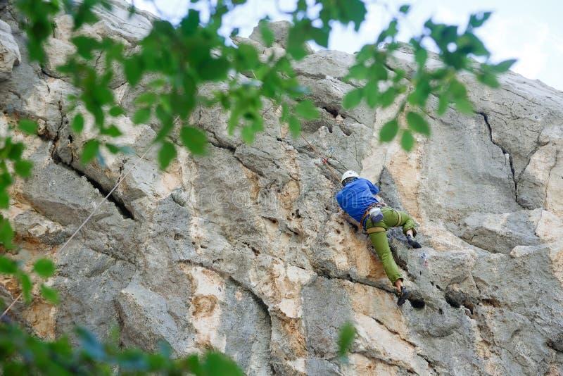 Junger Mann, der auf einer Wand klettert stockfoto