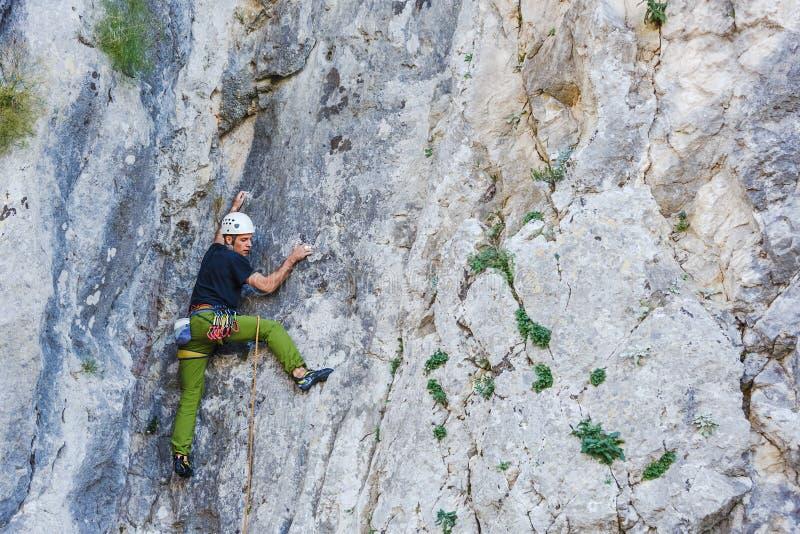 Junger Mann, der auf einer Wand klettert stockfotografie