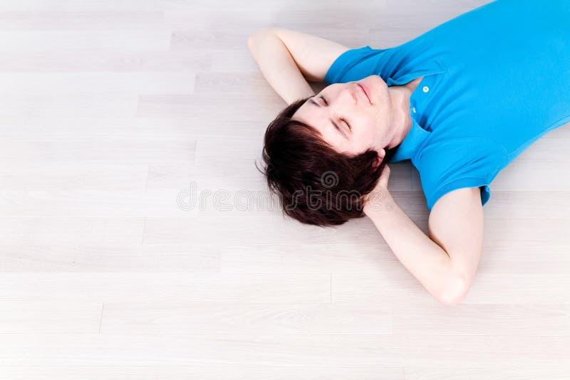 Junger Mann, der auf Fußboden liegt lizenzfreie stockfotos