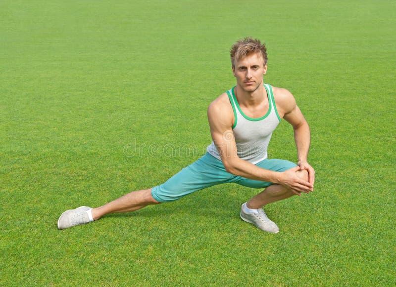 Junger Mann, der auf grünem Feld trainiert lizenzfreies stockbild