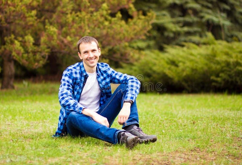 Junger Mann, der auf Gras im Park sich entspannt stockbilder