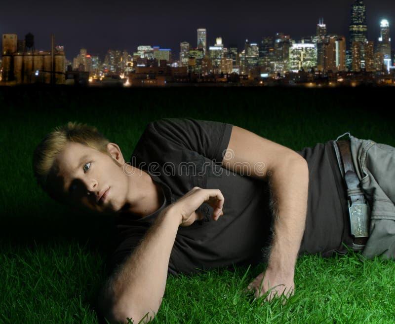 Junger Mann, der auf Gras legt lizenzfreie stockfotografie