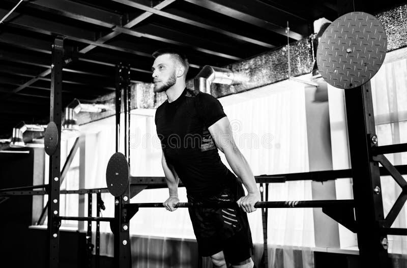 Junger Mann, der auf horizontaler Stange in der Turnhalle trainiert Männlicher erwachsener ausarbeitender Trizeps und Bizeps auf  lizenzfreie stockfotografie