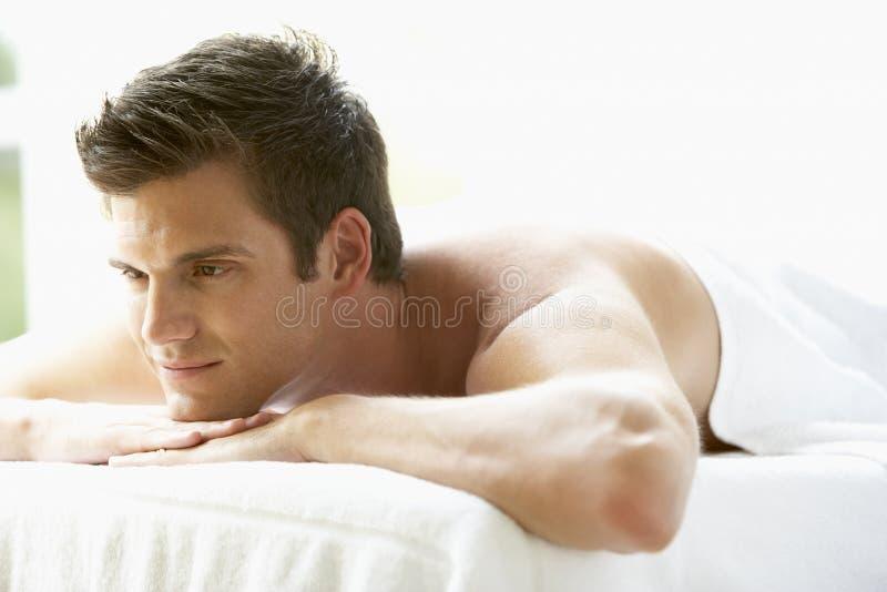Junger Mann, der auf Massage-Tabelle sich entspannt lizenzfreie stockfotos
