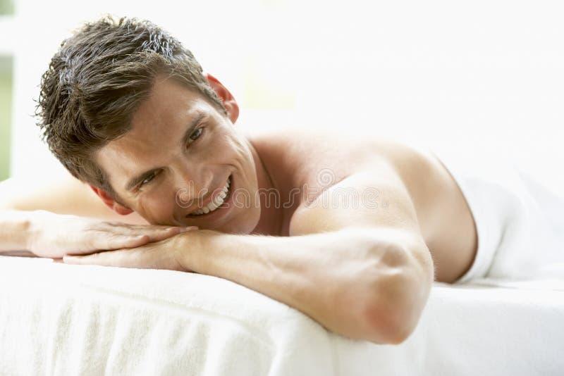 Junger Mann, der auf Massage-Tabelle sich entspannt lizenzfreies stockfoto