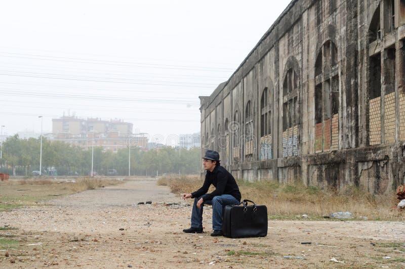 Junger Mann, der auf schwarzem Koffer sitzt lizenzfreie stockfotografie