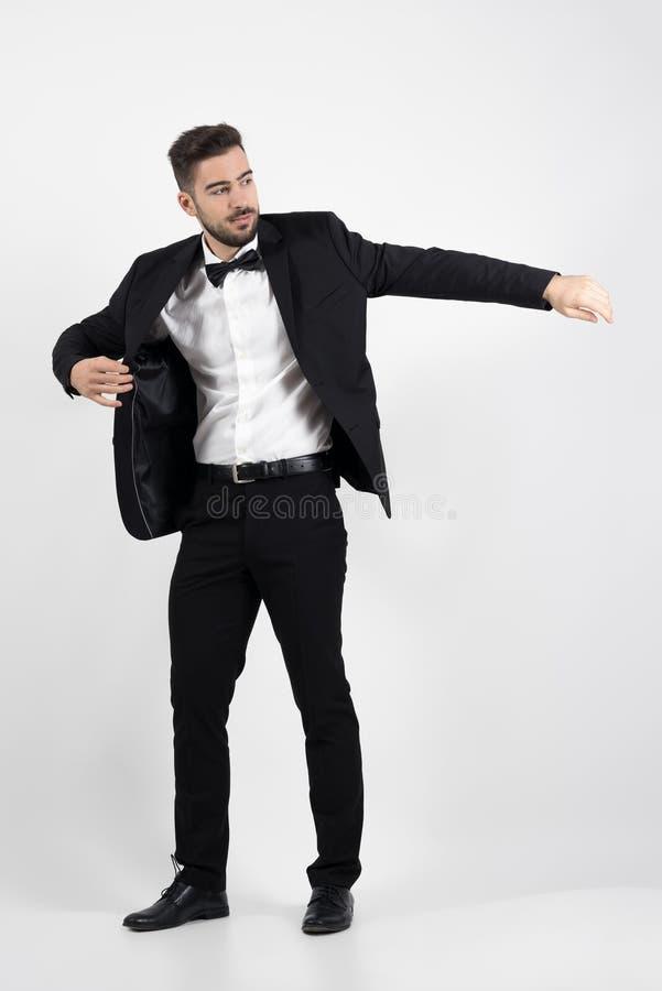 Junger Mann, der auf schwarzen Anzugssmokingsmantel sich setzt stockfotos