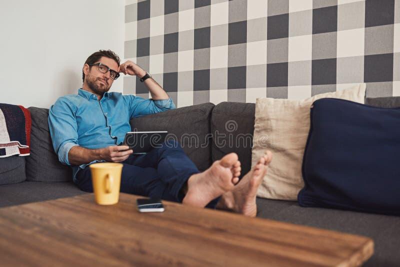 Junger Mann, der auf seinem Sofa unter Verwendung einer digitalen Tablette sich entspannt lizenzfreie stockbilder