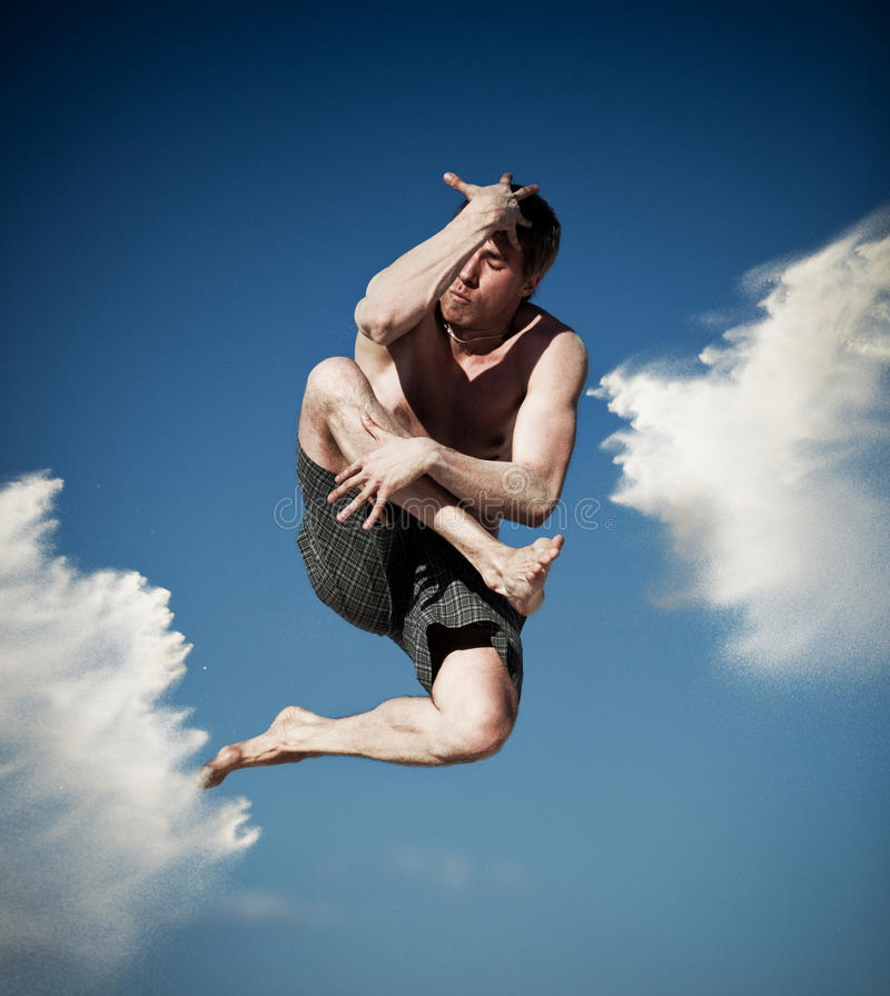 Junger Mann, der auf Strand springt stockbild