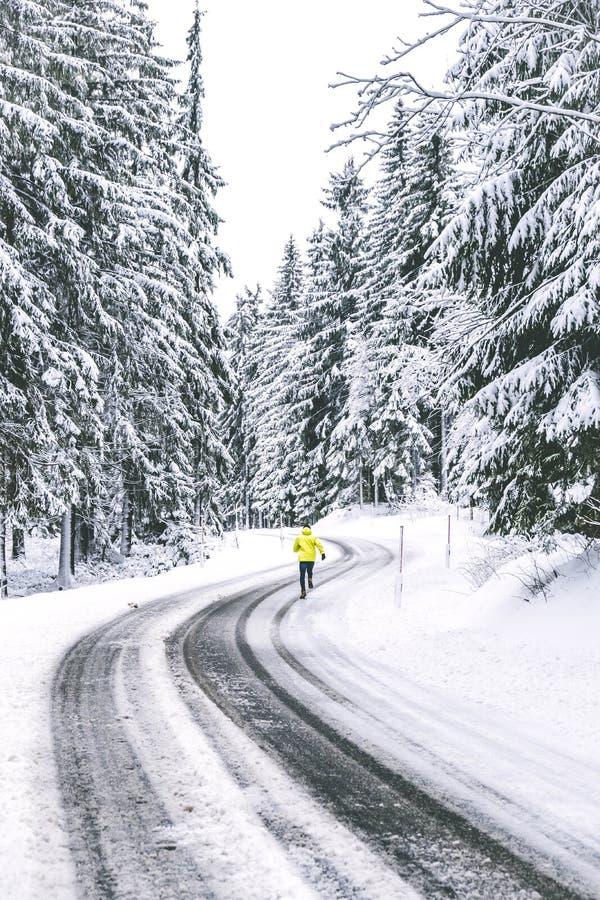 Junger Mann, der auf der Winterstraße läuft stockbild