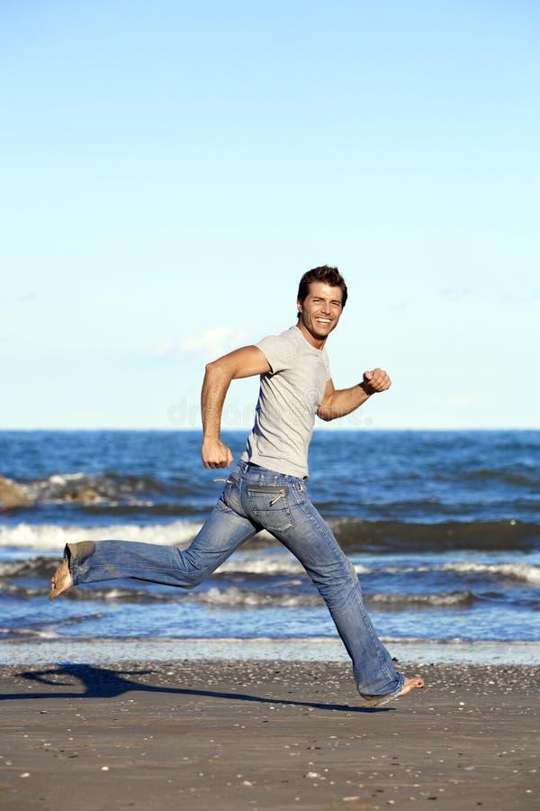 Junger Mann, der barfuß auf Strand läuft lizenzfreie stockbilder