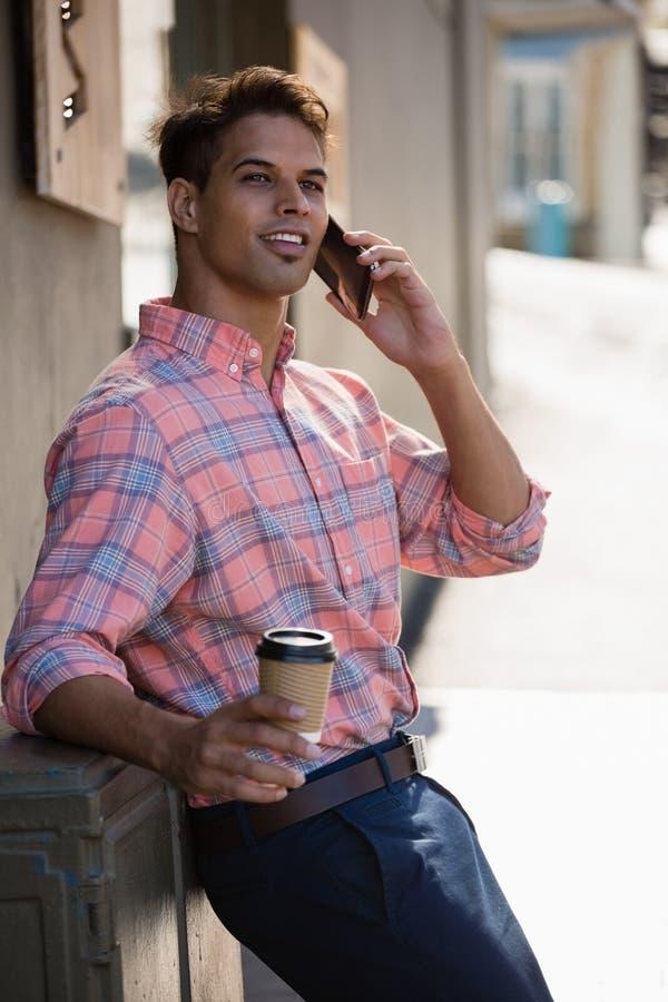 Junger Mann, der bei der Unterhaltung am intelligenten Telefon weg schaut stockfotos