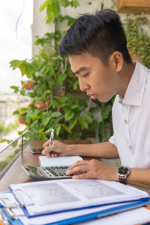 Junger Mann, der Berechnung auf Taschenrechner tut stockbild