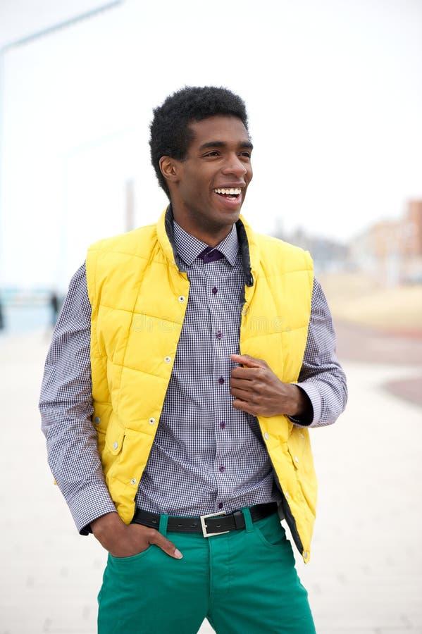 Junger Mann in der bunten Kleidung, die draußen steht lizenzfreie stockfotografie