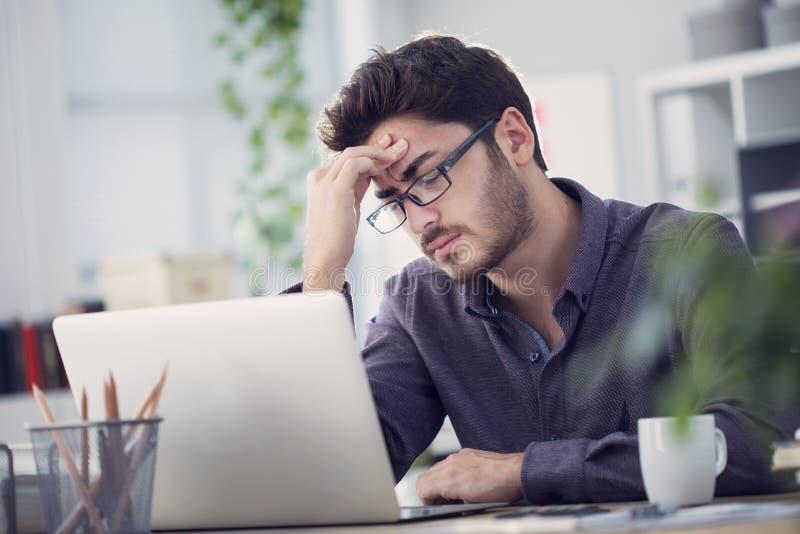 Junger Mann, der an Computer arbeitet und Kopfschmerzen hat lizenzfreie stockfotos