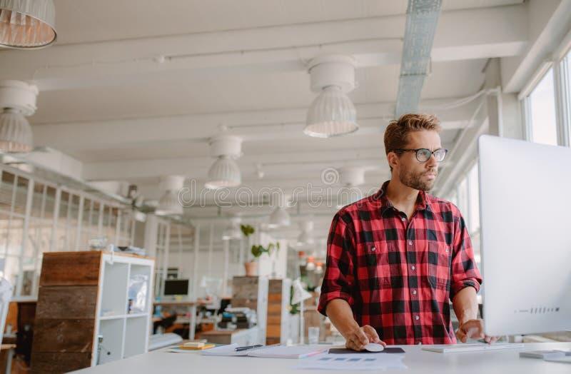 Junger Mann, der an Computer an modernem Arbeitsplatz arbeitet lizenzfreies stockfoto
