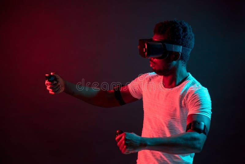 Junger Mann, der das aufpassende Video VR-Kopfhörers, lokalisiert auf dunkelrotem Doppellicht trägt lizenzfreie stockbilder