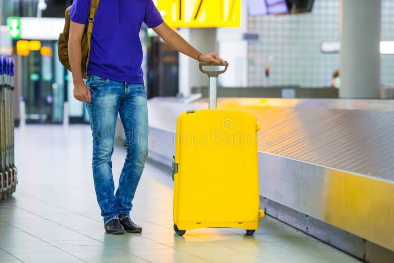 Junger Mann, der das Gepäck vom Gurt an nimmt stockfotos
