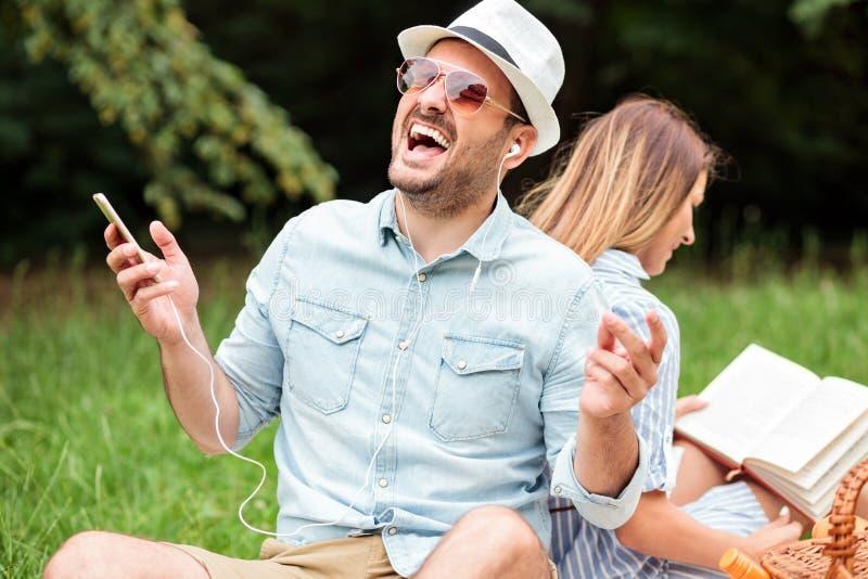 Junger Mann, der das Hören auf sein Lieblingslied genießt Sitzen zurück zu Rückseite mit seiner Freundin, die ein Buch liest stockfotografie