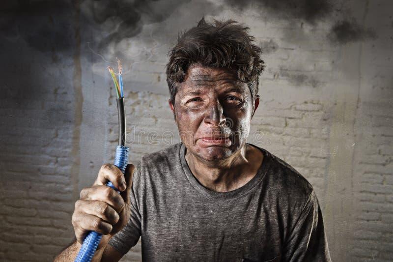 Junger Mann, der das Kabel raucht nach elektrischem Unfall mit schmutzigem gebranntem Gesicht im lustigen traurigen Ausdruck hält stockfotos