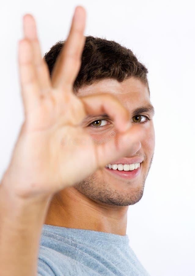 Junger Mann, der das okayzeichen auf weißem Hintergrund tut lizenzfreie stockfotos
