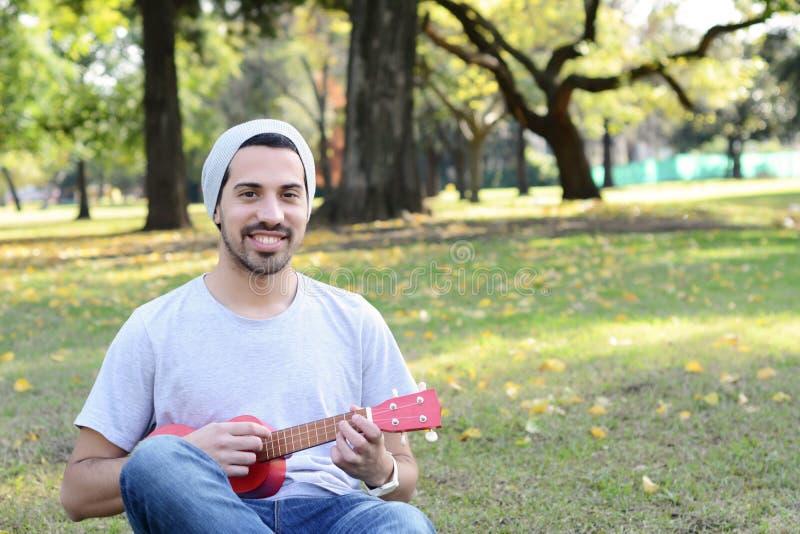 Junger Mann, der das ukelele in einem Park spielt lizenzfreies stockbild