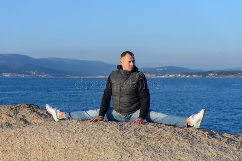 Junger Mann, der das Yoga sitzt in einer Schnur auf einem Felsen tut lizenzfreies stockfoto