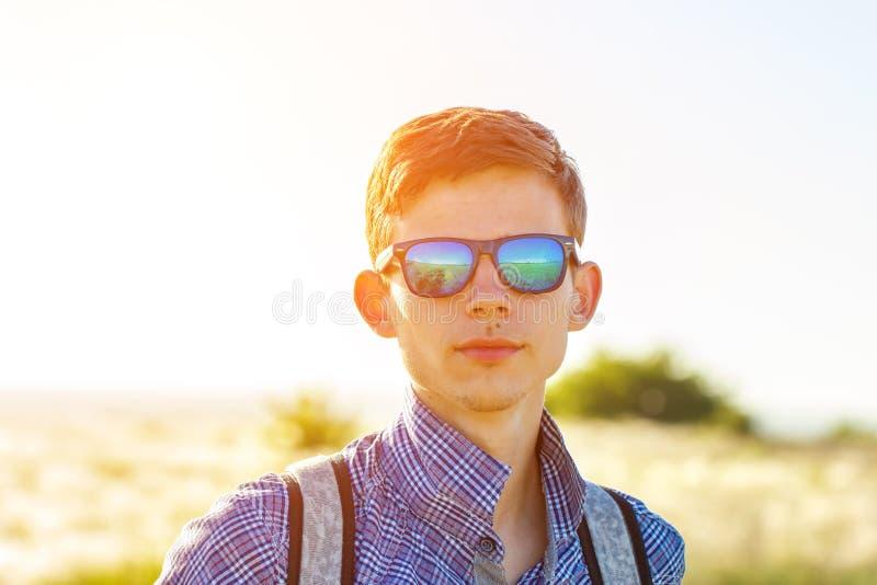 Junger Mann, der den Abstand auf einem sonniger Tageskonzept der Freiheit und des Tourismus untersucht stockfoto
