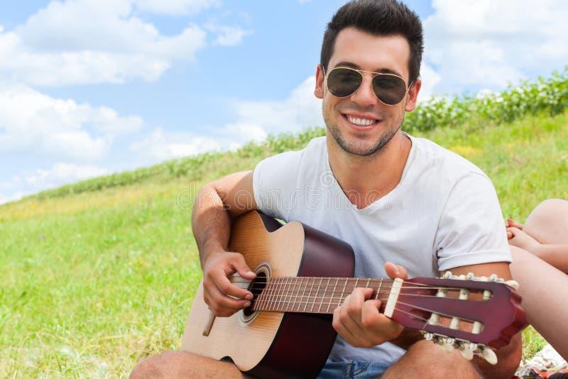 Junger Mann, der den Gitarrensommertag sitzend Picknick des grünen Grases im Freien spielt stockbild