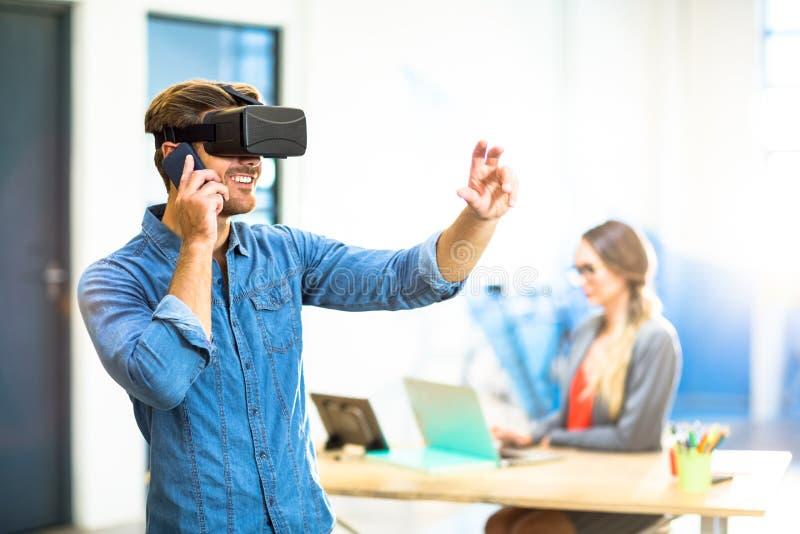 Junger Mann, der den Kopfhörer der virtuellen Realität bei der Unterhaltung am Telefon verwendet stockbilder