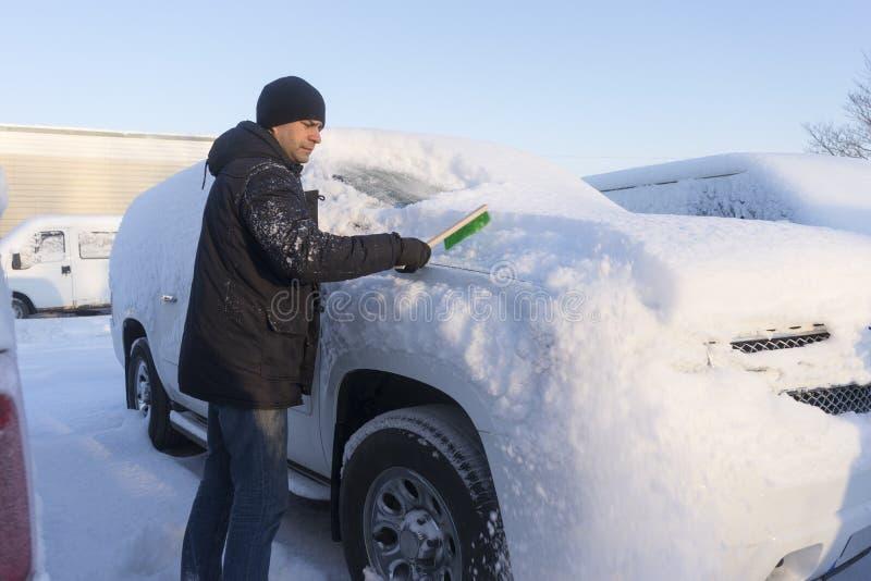 Junger Mann, der den Schnee vom Auto am sonnigen Wintertag bürstet stockbilder