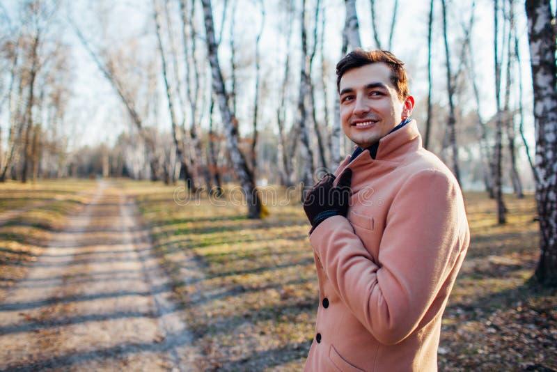 Junger Mann, der in den Wald in der Natur in einem Sahnemantel geht stockfotos
