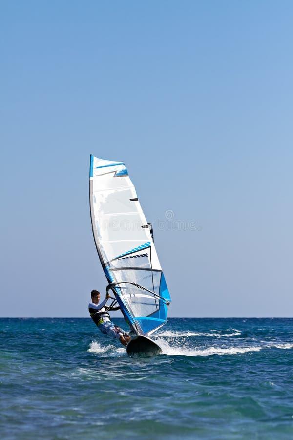 Junger Mann, der den Wind surft lizenzfreie stockbilder