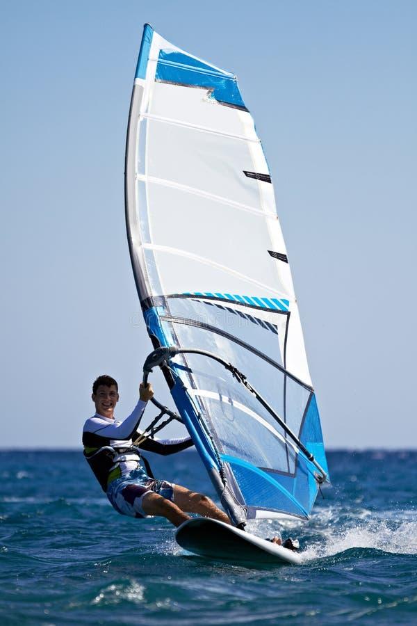 Junger Mann, der den Wind surft lizenzfreies stockbild
