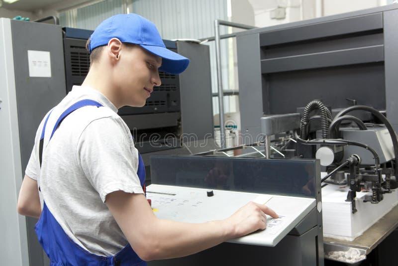 Junger Mann, der in der Druckfabrik arbeitet lizenzfreie stockfotos