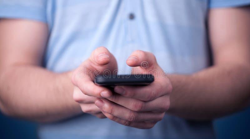 Junger Mann, der in der Hand smarthphone hält lizenzfreies stockbild
