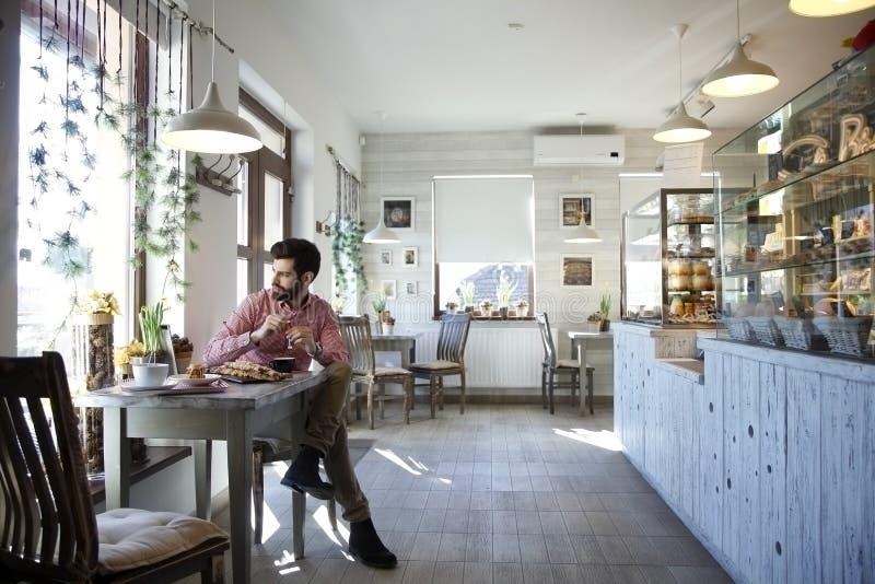 Junger Mann, der in der Kaffeestube sitzt. lizenzfreies stockfoto