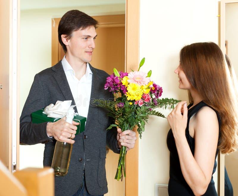Junger Mann, der der netten Frau Geschenke gibt stockbild