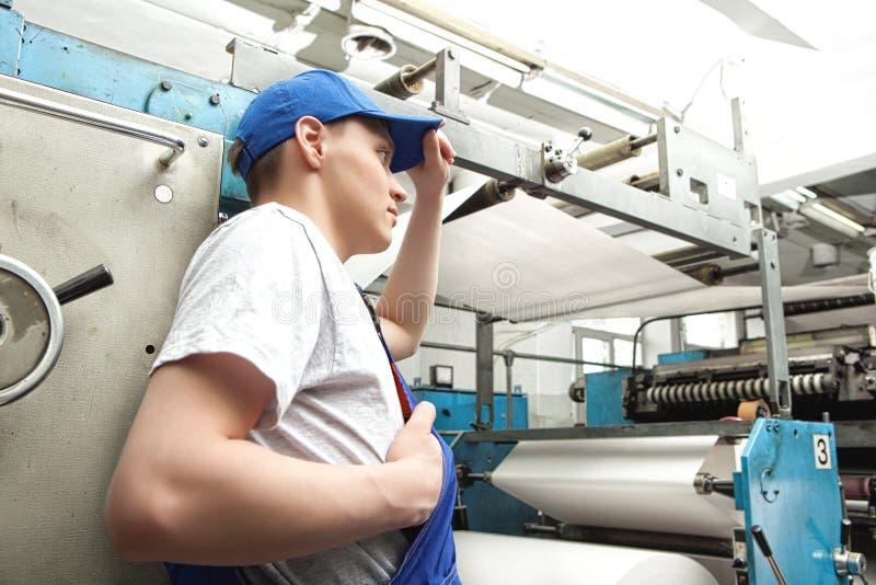 Junger Mann, der in der Zeitungsfabrik arbeitet lizenzfreies stockfoto