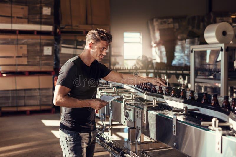 Junger Mann, der die Bierherstellung an der Brauerei überwacht stockbilder